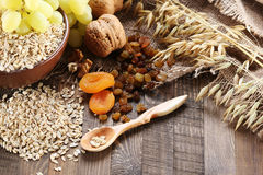 Oatmeal in a clay bowl, stalks of oats, dried apricots, raisins, Royalty Free Stock Image