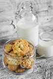 Oatmeal cookies with apples in a glass jar, a bottle of milk Royalty Free Stock Photography