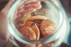 Oatmeal cookies in the Bank. A man looks in a jar with oat biscuits, and it's a magical moment, reminiscent of childhood Royalty Free Stock Image