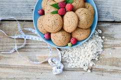 Oatmeal cookies in a bowl and raspberry next to measuring tape cereal. Oatmeal cookies in a bowl of berries, gooseberries and raspberries next to the measuring Stock Image