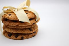 Oatmeal cookies with chocolate drops, tied with a golden ribbon, isolated on white background royalty free stock images