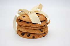 Oatmeal cookies with chocolate drops, tied with a golden ribbon, isolated on white background stock image