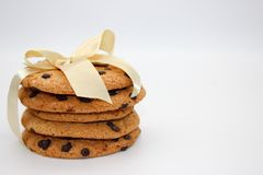 Oatmeal cookies with chocolate drops, tied with a golden ribbon, isolated on white background stock photography