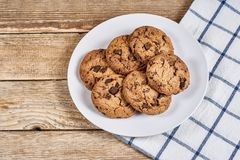 Oatmeal Chocolate Chip cookie. Oatmeal cookies with chocolate slices in white plate and napkin on a wooden background Stock Image