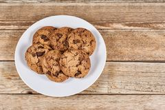 Oatmeal Chocolate Chip cookie. Oatmeal cookies with chocolate slices in a white plate on a wooden background Royalty Free Stock Photography