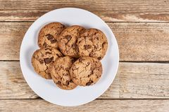 Oatmeal Chocolate Chip cookie. Oatmeal cookies with chocolate slices in a white plate on a wooden background Royalty Free Stock Photo