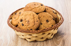 Oatmeal cookies with chocolate in wicker basket on table Stock Photos