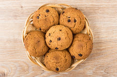 Oatmeal cookies with chocolate in wicker basket on wooden table Stock Photo