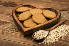 Oatmeal cookies and flakes on the wooden plate on the rustic surface. Oatmeal cookies and flakes on the wooden plate on the rustic wooden surface Royalty Free Stock Photography