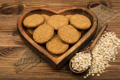 Oatmeal cookies and flakes on the wooden plate on the rustic surface. Oatmeal cookies and flakes on the wooden plate on the rustic wooden surface Stock Photo