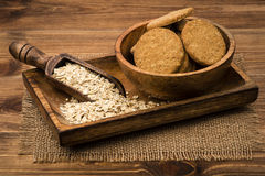 Oatmeal cookies and flakes on the wooden plate on the rustic surface. Oatmeal cookies and flakes on the wooden plate on the wooden rustic surface Royalty Free Stock Photo