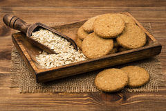 Oatmeal cookies and flakes on the wooden plate on the rustic surface. Oatmeal cookies and flakes on the wooden plate on the wooden rustic surface Stock Photos