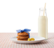 Oatmeal cookies and flowers on and bottle of milk Royalty Free Stock Photo