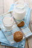 Oatmeal cookies and glass of milk on blue napkin Stock Images