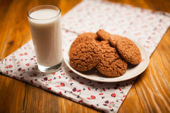 Oatmeal cookies and glass of milk on napkin on table Stock Image