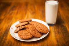 Oatmeal cookies and glass of milk on napkin on table Stock Photo