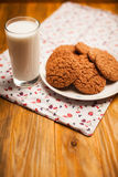 Oatmeal cookies and glass of milk on napkin on table Stock Photos