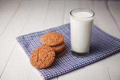 Oatmeal cookies and glass of milk on napkin on white table Royalty Free Stock Photos