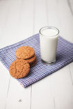 Oatmeal cookies and glass of milk on napkin on white table Stock Photo