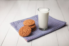 Oatmeal cookies and glass of milk on napkin on white table Royalty Free Stock Images
