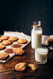 Oatmeal Cookies and Glass of Milk. Oatmeal Cookies with Raisins and Glass of Milk for Breakfast. Some Cookies on Parchment Paper with Bottle on Backdrop. Copy Stock Photography