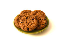Oatmeal cookies on the green saucer on the white background. Royalty Free Stock Photos