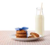 Oatmeal cookies, halves of cookies on plate, bottle of milk Stock Image