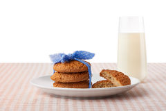 Oatmeal cookies, halves of cookies on plate, glass of milk Stock Image