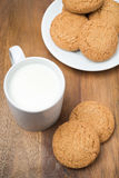 Oatmeal cookies and a mug of milk on a wooden board Royalty Free Stock Photos
