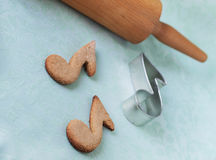 Oatmeal cookies shaped as notes. On a green background Stock Photography