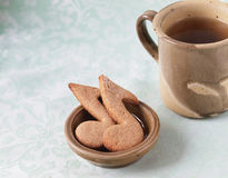 Oatmeal cookies shaped as notes. On a green background and a cup of tea Stock Photos