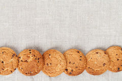Oatmeal cookies on the texture of flax Stock Photos