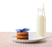 Oatmeal cookies on white ceramic plate and bottle of milk Stock Photography