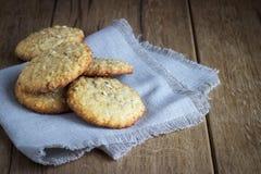 Oatmeal cookies on white linen napkin on wooden Royalty Free Stock Photo