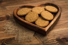 Oatmeal cookies  on the wooden plate on the rustic surface. Oatmeal cookies  on the wooden plate on the rustic wooden surface Stock Image