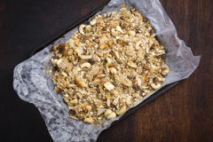Oatmeal crunch in the tray on the dark wooden background Stock Image