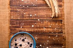Oatmeal with currant in blue bowl with Royalty Free Stock Photo