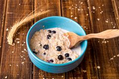 Oatmeal with currant in blue bowl with Stock Photography