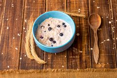 Oatmeal with currant in blue bowl with Royalty Free Stock Photos