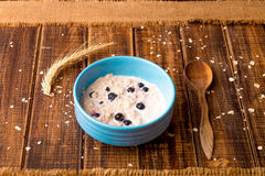 Oatmeal with currant in blue bowl with spoon on wooden background. Rustic style. Healthy breakfast. Close up. Royalty Free Stock Photos
