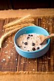 Oatmeal with currant in blue bowl with Stock Photo