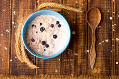 Oatmeal with currant in blue bowl with spoon on wooden background. Rustic style. Healthy breakfast. Top view. Royalty Free Stock Photo