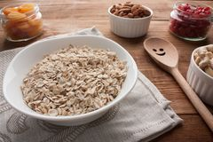 Oat flakes in bowl with dried apricots, dried cherries, almonds, cashews in jars on wooden table with wooden spoon. Oatmeal with dried apricots, dried cherries Royalty Free Stock Images