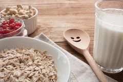 Oatmeal with dried cherries, cashews, milk and a wooden spoon on wooden table. Oatmeal with dried cherries and cashews on wooden table whith napkin. Glass of Stock Photo