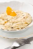Oatmeal with dried fruits and orange in white bowl Stock Image