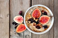Oatmeal with figs, cranberries and walnuts over rustic wood. Oatmeal with red figs, cranberries and walnuts in a bowl, above view on rustic wood Royalty Free Stock Photo