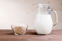 Oatmeal flakes in a bowl next to the milk carafe Stock Photos