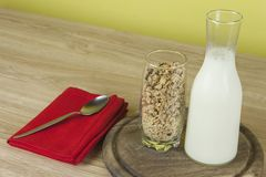 Oatmeal flakes in a glassful next to the milk carafe. Healthy breakfast with fiber. Stock Images