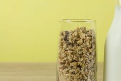 Oatmeal flakes in a glassful next to the milk carafe. Healthy breakfast with fiber. Royalty Free Stock Photos