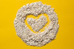 Oatmeal flakes for health. vegetarian food for breakfast on a colored background. organic product. heart concept in a stock image